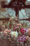 Photograph of flower arrangements in front of a metal cross in graveyard