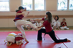 Albany CA Mixed-age class of children at Tae Quan Do demonstration, showing how to break a board with a kick
