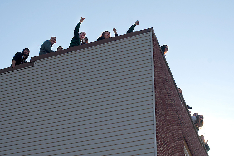 Onlookers shout from a roof top on Union street during the homecoming parade on saturday. Photo by: Ross Brinkerhoff..