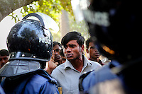 A factory worker argues with police as he tries to collect his wages from the remains of the factory. His brother was killed in the blaze. At least 112 people died, and more than 100 were injured at a fire at the Tazreen Fashions textile factory in Dhaka. Bangladesh's garment industry has a notoriously bad fire safety record; if the right precautions had been taken, the fire could have been prevented.
