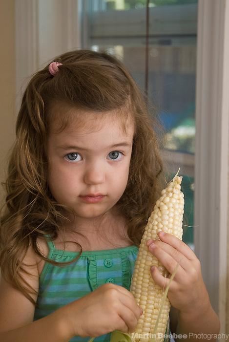 A three-year-old girl shucks corn