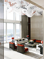 A spectacular custom lighting sculpture acts as a canopy above one social seating group shaped with Christian Liaigre's velvet sofas and spicy red chairs. The soaring double height windows flood the room with light.
