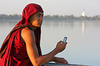 Myanmar, Burma, Mandalay.  Buddhist Monk Taking Cell Phone Picture on the U Bein Bridge, Amarapura.