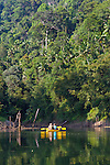 Ranforest Camp Elephant Hills Luxury Floating Tented Camp in the rainforest in Southern Thailand.  A couple touring the jungle by kayak on Cheow Larn Lake.