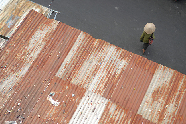 A woman walks through a market wearing a traditional vietnamese hat