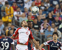 Toronto FC forward Jeremy Brockie (22) and New England Revolution defender Andrew Farrell (2) battle for head ball. In a Major League Soccer (MLS) match, Toronto FC (white/red) defeated the New England Revolution (blue), 1-0, at Gillette Stadium on August 4, 2013.