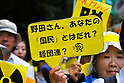 Tokyo, Japan - June 17: A woman held a sign, which said &quot;Priministor Noda, Who's Your People, Keidanren?, or Japanese Business Federation,&quot; during a demonstration against nuclear power plants in Japan at Mitaka, Tokyo, Japan on June 17, 2012. As Japanese Government decided to restart Oi Nuclear Power Plants No.3 and 4 in Fukui, people spoke up against the restart throughout the nation. .