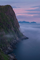 Summer ocean fog dritfs over mountains of Skolmen at midnight, Unstad, Vestvågøy, Lofoten Islands, Norway