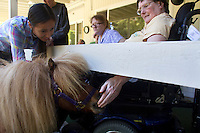 Brooke Ferguson (left) and miniature horse, lady Bug, visit with residents at the Park Ridge Skilled Nursing Center in Shoreline, Washington on July 10, 2014. Veterinarian Dana Bridges Westerman of Professional Equine Therapeutic arranges the therapy visit every year.