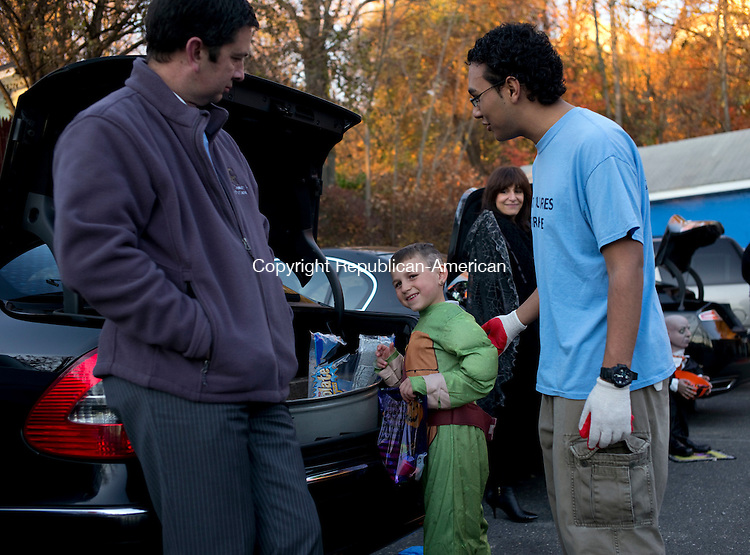 Waterbury, CT- 30 October 2015-103015CM04- Kobe Bedat, 5, of Waterbury dons a Ninja Turtles costume as he collects candy from Atty. Eric Brown of Waterbury at the Boys and Girls Club of Greater Waterbury on Friday. With Bedat is counselor, Edwin Torres.  The Boys & Girls Club of Greater Waterbury hosted a Halloween party for its members an event which included a haunted house, Halloween themed crafts, Halloween movies and snacks.    Christopher Massa Republican-American