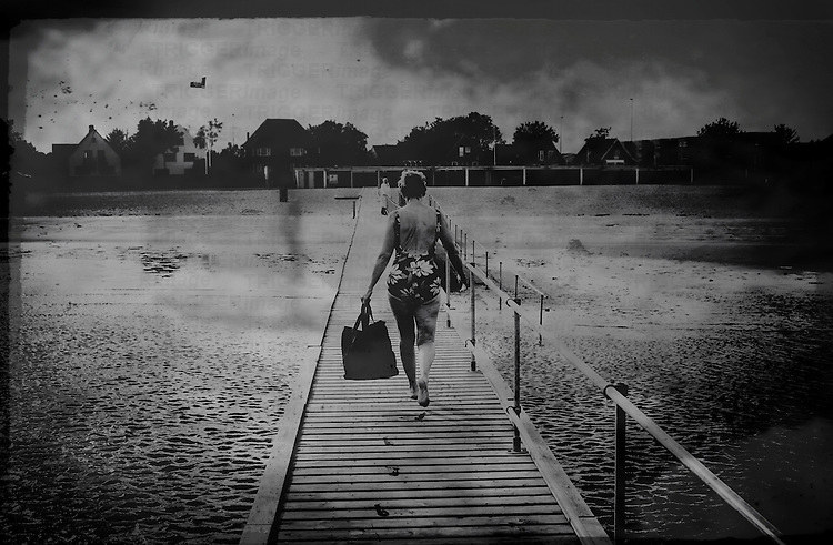 A middle aged woman wearing a swimming costume carrying a bag walking along a wooden jetty at the seaside