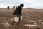 SHILAKAY, IRAQ: Syrian smugglers on the 4 hour walk from Iraq into Syria...Due to the recent conflict in Syria there is a gasoline shortage in the country. Syrian smugglers purchase gasoline in Iraq and smuggle it into Syria for a profit of about $0.40 per liter. Smugglers carry between 10 and 30 liters per person on the 7 hour roundtrip journey that often takes them through frozen mud and snow...Photo by Aram Karim/Metrography
