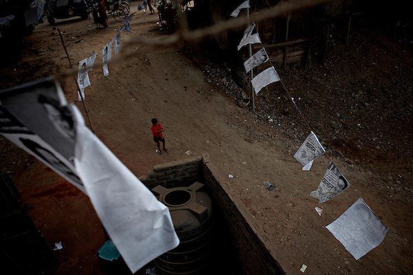A boy surrounded by election posters, Mohammadpur, Dhaka, Bangladesh...In the Mohamadpur slums the skies is covered by election posters as it is illegal to put them on walls, the posters are hung between buildings, lampposts or any other structure that can support them...Bangladesh has finished with two years of emergency rule. The election results is compared to the landslide of 1970 that led to war and independence from Pakistan. .When preparations for the election started in late 2006, violent street-protests started, and led to a military backed interim government until the election happened under heavy security and watchful eyes on December 29th 2008...The past two years have seen a decrease of crime and corruption but also sparked violent student protests and curfews. Today  most people seem to be happy to return to some sort of normality. But in one of the poorest countries in the world where 80% live for less than a dollar a day, does it really matter who is in power? The circus is over, back to reality and putting food on the table...A blogger  from dhaka is quoted Ó we prefer messy democracy to military ruleÓ...Is this the end of night, a new dawn or yet another dusk?..Photo by: Eivind H. Natvig/MOMENT *** Local Caption ***
