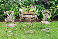 Backyard flea market finds, antique metal furniture on lawn with container planter of flowers