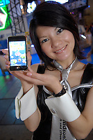 """A promotion girl for software maker Hudson holding software for i-pods and i-phones called """"Catch the Egg""""."""