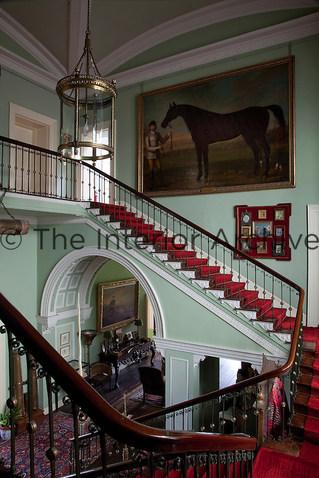 The scarlet carpeted double flight staircase winds up through the neo-classical hall