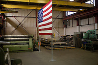 An American flag erected by the Romney campaign stands in the background of a Romney campaign event to begin at Gilchrist Metal Fabricating in Hudson, New Hampshire, on Jan. 9, 2012.  Romney is seeking the 2012 Republican presidential nomination.