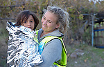 A volunteer from Norway carries a refugee girl near Molyvos, on the Greek island of Lesbos, on October 30, 2015. The girl came on a boat full of refugees that traveled to Lesbos from Turkey. The boat was provided by Turkish traffickers to whom the refugees paid huge sums to arrive in Greece.