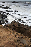 The original image of waves and rocks peppered with tafoni formations.