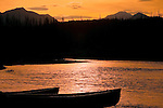 Two canoes silhouetted against water of the North Fork of the Flathead River on the boundary of Glacier National Park