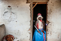 Witchdoctor Fage Chombe (53)in the doorway of her house in Samora Machel. Fage says that her spirit Bande came into her body the day after one member of her family poisoned himself only to later resurrect from himself from the dead as a spirit.