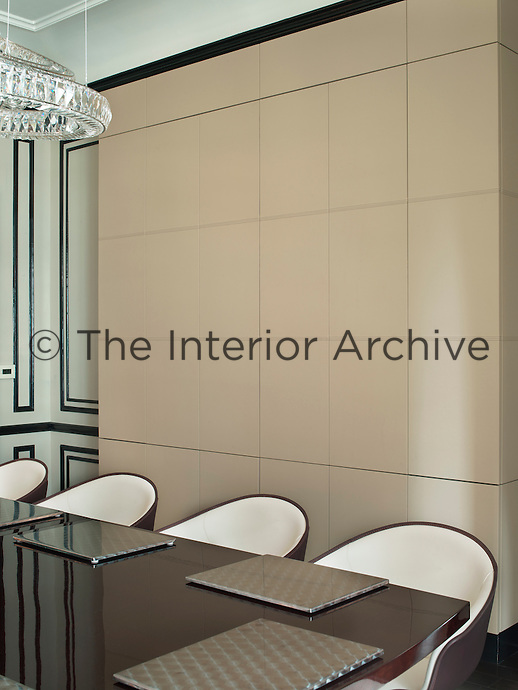 A leather-covered media wall conceals a large television and four Breitling clocks, while the placemats on the dining table are made of metal engine-spin