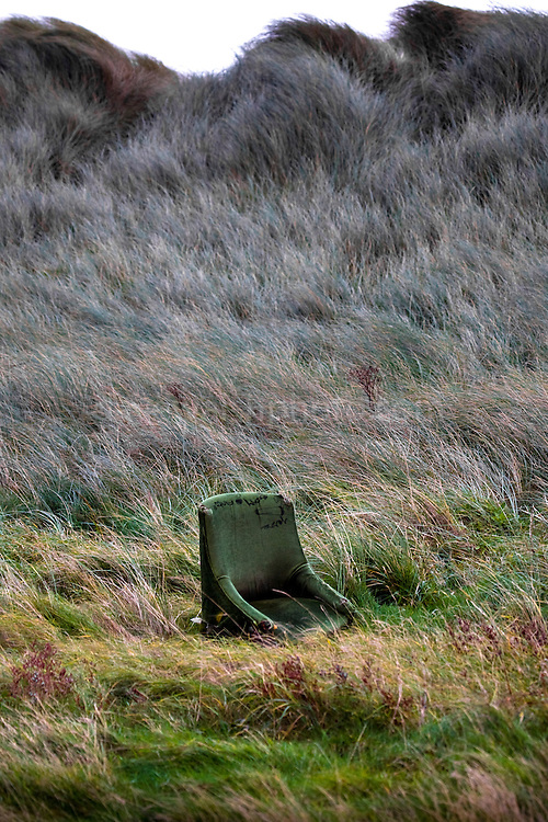 Abandoned chair on Bull Island, Dublin, camouflaged amongst the marram grass. ..Bull Island is a UNESCO protected biosphere reserve in the Northern suburbs of Dublin. It features two golf clubs, and Dollymount beach, used for kitesurfing and other outdoor activities. Wildlife includes seals and bird life.<br />