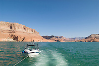 small ski boat being pulled by houseboat on Lake Powell