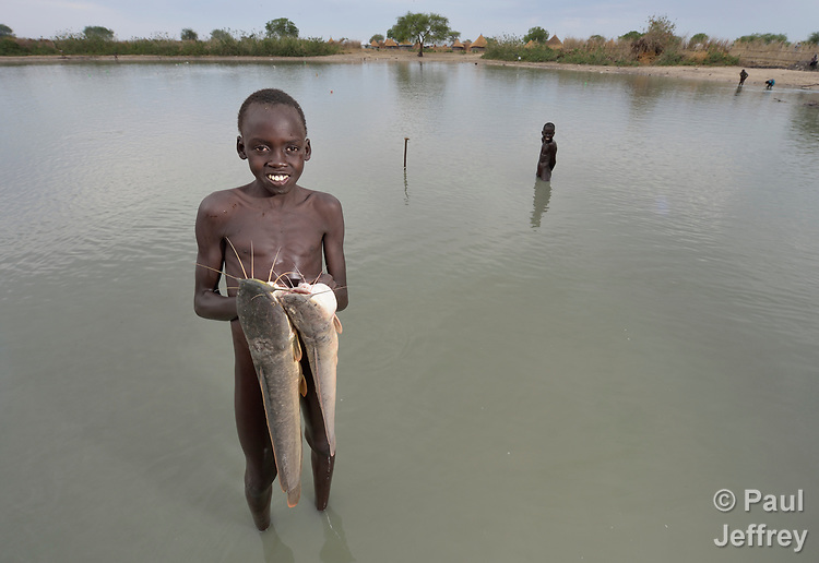 Marial Majak, 13, displays fish he caught in Poktap, a town in South Sudan's Jonglei State where conflict, drought and inflation have caused severe food insecurity. The Lutheran World Federation, a member of the ACT Alliance, is helping families tackle food problems, including by providing cash for the purchase of fishing line and hooks. This boy's family fled the region when war broke out in 2013, living internally displaced elsewhere in the country until returning at the end of 2016.<br /> <br /> Parental consent obtained.