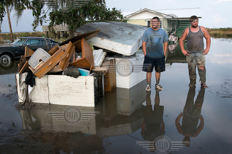 Two brothers stand outside their home in Louisiana. Their belongings are piled up outside due to their house being flooded, the cause of this being coastal erosion.