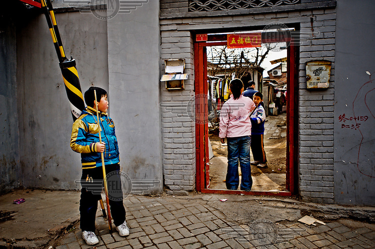 A boy stands by a doorway in a Beijing hutong.