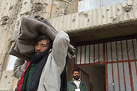 Russian Cultural Palace Kabul. The building was destroyed by the Mujahadeen during the Afghan civil war. Hundreds of people use the building to smoke and inject heroin. The Welfare Association for the Development of Afghanistan (WADAN) has reclaimed part of the building and turned it into a rehabilitation clinic. A volunteer (ex addict) takes blankets to a newly opened sleeping area.