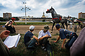 Stable assistants watch a harness race on the sidelines of Moscow's Hippodrome race course. .Harness racing is a form of horse-racing in which the horses race in a specified gait, pulling two-wheeled carts called sulkies.