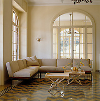 This light and airy room which features a geometric tiled floor is funished with an L-shaped sofa and a pair of tray tables