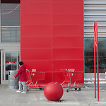 A women in a red parka passes a red cart in front of a red panel of a national store chain