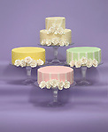 white rose icing on four different colors of wedding cakes