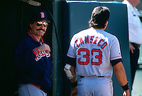 OAKLAND, CA - Manager Kevin Kennedy of the Boston Red Sox jokes with Jose Canseco in the dugout during a game against the Oakland Athletics at the Oakland Coliseum in Oakland, California in 1995. Photo by Brad Mangin