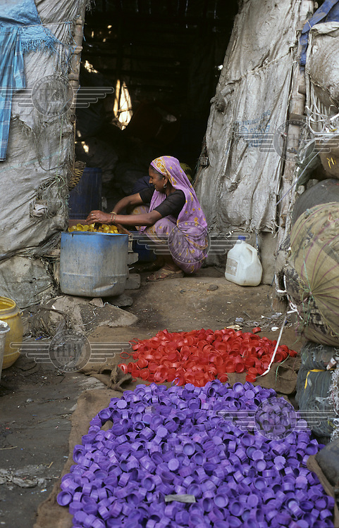 A woman recycles plastic waste in a slum area of Kolkata..