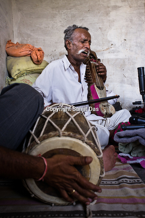 66-year-old Manganiyar artist, Lakha Khan sings and plays the Sarangi while his eldest son, Dane Khan (left) accompanies him with Dholak in their house in Raneri village of Jodhpur district in Rajasthan, India. Photo: Sanjit Das/Panos