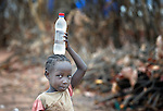 A girl carries water on her head in the Ajuong Thok Refugee Camp in South Sudan. The camp, in northern Unity State, hosts thousands of refugees from the Nuba Mountains, located across the nearby border with Sudan.