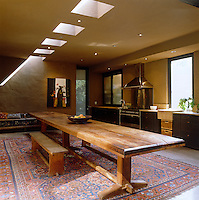 A row of skylights throws light on to the long wooden kitchen table