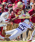 Florida State's fullback Freddie Stevenson goes up and over Louisville defenders Josh Harvey-Clemons (25) and Stacy Thomas, left, in the second half of an NCAA college football game against Louisville in Tallahassee, Fla., Saturday, Oct. 17, 2015. Florida State defeated Louisville 41-21. (AP Photo/Mark Wallheiser)