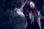Young woman with long red hair blowing in wind wearing a blue blouse standing alone outdoors with eyes closed
