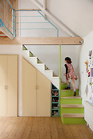 A child runs up the open staircase from the kitchen