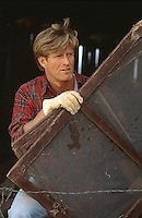All American man working on a ranch by carrying wooden screens in a barn