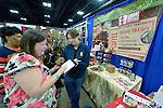 Bekah Forni (right) of Equal Exchange helps Shirley McNichol of Texas sign a credit card purchase for fair trade products during the United Methodist Women Assembly in the Kentucky International Convention Center in Louisville, Kentucky, on April 25, 2014.