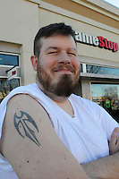 NWA Democrat-Gazette/FLIP PUTTHOFF<br /> Lee Tate shows his tattoo on Friday Jan. 16 2015 outside his business at Pinnacle Hills Promenade in Rogers.