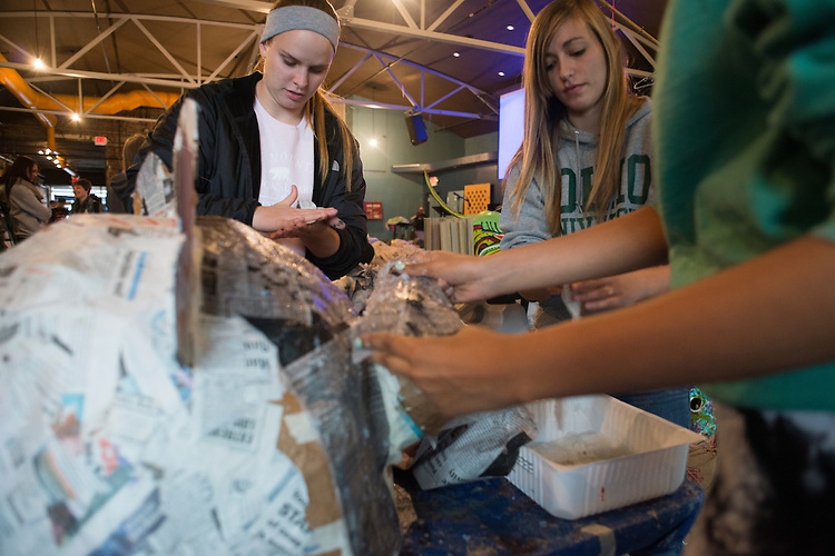 Ohio University students Taylor Stano (left), Julia Golias, and Akiah Muhammad paper mache a giant puppet head at Honey for the Heart located at 29 E. Carpenter St. in Athens, Ohio.