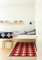 A pair of children's beds are dove-tailed to save space in this small clapboard attic bedroom