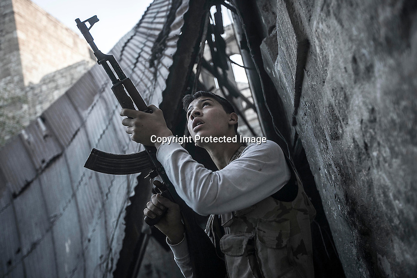 In this Saturday, Nov. 03, 2012 photo, a rebel fighter belonging to the Qatebee Sokor Al-Islam watches over a building windows as he awaits for the loyalists to President Bashar Al-Assad to show up while carrying out a coordinated attack by mortar and tank artillery and warplanes during heavy clashes in the nearby Castel Harami battlefield in the Jdeide district of Aleppo, the Syrian's largest city. (AP Photo/Narciso Contreras).